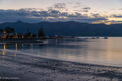 Akaroa beach sunset (Andrs Guerrero) Tags: akaroa anochecer atardecer bankspeninsula costa harbour mar newzealand nuevazelanda oceana peninsuladebanks puerto sea sunset playa beach