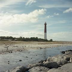 Yashica - lighthouse img198 (T. Brian Hager) Tags: yashica yashica124g 120 120film film analog square fuji color fujipro400h epson epsonv600 water lighthouse barnegatlighthouse shore nj clouds rocks