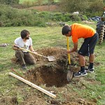 Two students working together to dig a hole.