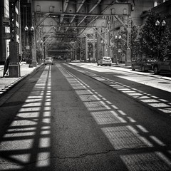 """Last couple days may make you wonder but the sun does shine in Chicago. The """"L"""" presents so many great opportunies. (GDMetzler) Tags: street city summer chicago cars lines train blackwhite illinois shadows samsung sunny friday westloop thel blackandwhitephotography gdmetzler patternssigns"""