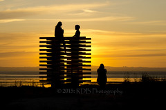 Sunset Sculpture 3 (ArdieBeaPhotography) Tags: ocean boy sunset wild sky sculpture orange cloud beach girl grass silhouette yellow thames climb rainbow alone waterfront gulf spectrum dusk talk multicoloured hills mum together sit fennel firth moanataiari