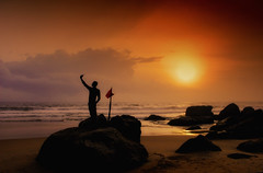 The Selfie Guy (Sudhakar Madala) Tags: red orange sun water sea silhouette mar beach sky nature beautiful boulders rock flag people evening canon eos dramatic unusual