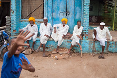 Elders chatting and a dynamic kid (Scalino) Tags: india karnataka travel trip badami durga temple fromtherickshaw streetphotography street surprise unposed onspot passingby old men chatting turban orange safran white elders village kid hand