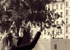 **Bird Fun** (**klaracolor**) Tags: paris klara klarathomas klaracolor canon canon40d france sparrow sparrows bird birds woman laughing house building people feeding feedingbirds laugh tree monochrome