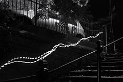 Man With A Bike (h_cowell) Tags: monochrome street lighttrail blackandwhite steps outdoors railing contrast pattern abstract night evening lowlight lowkey nikefex atmospheric panasonic gx7 longexposure appicoftheweek