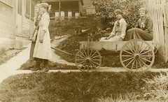 Girls Pulling Themselves on a Wagon (Alan Mays) Tags: old yards girls vintage buildings children clothing funny humorous photos antique wheels humor fences ephemera hills riding photographs dresses postcards amusing hillside pulling trickphotography wheelbarrows wagons surprising foundphotos doubleexposures beehives perplexing rppc trickphotos realphotopostcards photographicamusements vptp