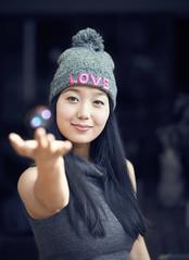 Reaching (bovinemagnet) Tags: portrait woman girl smile asian au longhair australia bubbles victoria bubble beanie