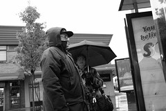 (L D Middleton) Tags: street old bw white black up rain umbrella photography waiting couple warm fuji wrapped busstop and hood fujifilm droylsden x100t ldmiddleton