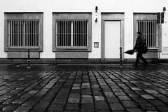 As the rain washed the street (Isengardt) Tags: rain regen umbrella regenschirm mann man people mensch wash waschen clean sauber pfalsterstein stein stone komposition composition street strase fenster windows vergittert barred black white monochrome monochrom schwarz weiss bw sw esslingen badenwürttemberg deutschland germany europe europa olympus omd em1 1250mm