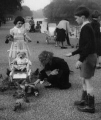 Regents Park (theirhistory) Tags: girl boy pushchair birds food dress jumper shorts socks boots raincoat park londom england teddy