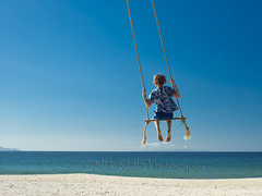 Boxing Day, 2015, Swinging 2 (ArdieBeaPhotography) Tags: ocean blue boy sea sky white beach coast high sand swing shore