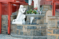 At The Feet Of The Virgin (henulyphoto) Tags: red white plant flower saint statue rock fence praying virgin kneeling contemplating