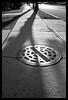 MC W. Rokkor-X 28mm f/2.8, K (Ebanator) Tags: minolta28mmlens minoltamcwrokkorx28mmf28 rokkor28mmf28 sonya850 mono0chrome street streetphotogrpahy woodridgenewjersey woodridgenj manholecover sidewalk shadows concrete