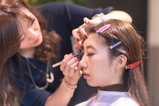 Young Japanese girl making up in beauty salon
