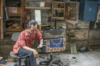 #WWPW2015  Killing time An old-fashion barber, checking his text message, near the Old City of Jakarta, Indonesia