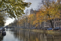 Autumn in Amsterdam (Jan Kranendonk) Tags: holland dutch amsterdam canal boats houses buildings sunny autumn fall water historical old sky street travel city landmark scenic corner netherlands reflection flag warehouses homes apartments houseboat herfst gracht bomen ngc