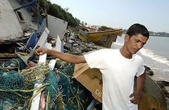 Captain examines his destroyed boats off Balapitya, Sri Lanka