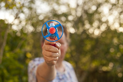 Woman pointing toy gun at camera (Jim Corwin's PhotoStream) Tags: wood stilllife abstract game childhood horizontal youth table fun toy photography colorful pattern patterns nobody stack indoors nostalgia entertainment simplicity leisure recreation multicolored amusements enjoyment stacked spinners skill selectivefocus woodtable playgame culturalartifacts closeupview smallgroupofobjects childhoodgame studioimage simplegame multicoloredjacks
