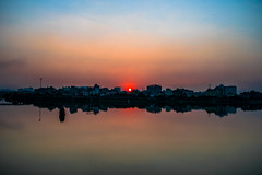 | SUNSET - Dhaka, Bangladesh | (mdanwarhossain) Tags: sunset sun red sky landscape building outdoor colors yellow blue water reflection city symmetry