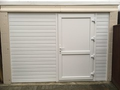 Garage door opening infill with upvc side door and cladding.