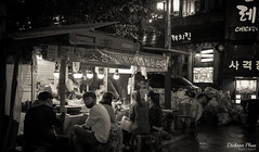 Late night supper (gunman47) Tags: 2016 asia asian b bw hongik korea korean mono monochrome october rok republic seoul sepia south w black candid food hawker hongdae late night people photography rain roadside stall street supper tourist university white    southkorea crowd