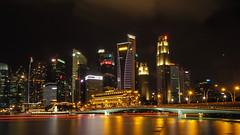 Night Lights (elenaleong) Tags: marinabay skyline landmark architecture nightscape le goldenlights reflections jubileebridge elenaleong singapore trails boattrails merlionpark