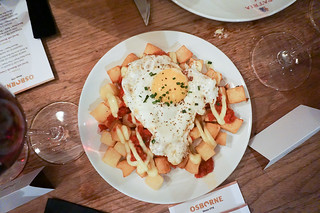 Spanish style potatoes with fried egg and spicy tomatoes