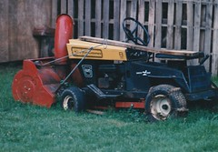 AN OLD TRACTOR/SNOWBLOWER (richie 59) Tags: ulstercountyny ulstercounty newyorkstate newyork unitedstates townofesopusny townofesopus tractor spring richie59 stremyny stremy outside backyard yard olddays oldpicture oldphoto flim cougartractor may231986 may1989 1986 america 1980s oldtractor oldlawntractor lawntractor snowblower hudsonvalley midhudsonvalley midhudson nystate nys ny usa us junk oldshit crap grass 35mmfilm 35mm filmphotography photograph oldphotograph