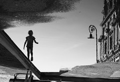 Balancing act (mkorolkov) Tags: street streetphotography puddle puddlegram balancing reflection silhouette girl playing blackandwhite monochrome fujifilm xe1 xc50230