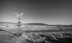 Crossroads (claugrodriguez) Tags: deathvalley tronapinnacles bw blackandwhite crossing desert landscapephotography monochrome mountain outdoor railway road stopsign california usa