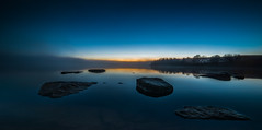 Distant glow (Tore Thiis Fjeld) Tags: norway nowember evening distant glow maridalsvannet oslo fog mist lake surface rocks sky afterglow panorama nikon d800 samyang 14mm forest nature wilderness outdoors quiet colors