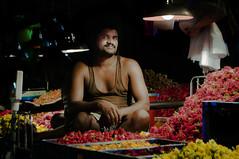 Market musings (Sriraam Kalingarayar) Tags: light red portrait flower dark market vendor koyambedu sriraam sriraamkalingarayar