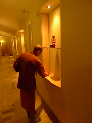 Tan Suvijjano cleans the hallway shrine