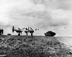 "Loaded with members of a U.S. Navy beach battalion, a U.S. Arm ""Duck ""scoots past a P-38 spotted on a airstrip quickly fashioned on the beachhead after Allied landing in Normandy. (HarryKidd) Tags: ww2 landingcraft dday omahabeach"