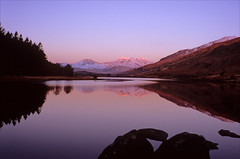 sunrise reflections (Ron Layters) Tags: snowdon sunrise alpenglow morning llynnaumymbyr lake reflection snow hill mountain water boulders silhouette trees winter cold red pink yellow glowing ylliwedd ice landscape snowdonia capelcurig conwy wales cymru unitedkingdom slidefilmthenscanned slide transparency fujichrome velvia leica r6 leicar6 ronlayters