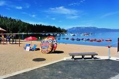 Zephyr Cove, Nevada (Joe Lach) Tags: trees beach bench boats toys sand nevada laketahoe umbrellas pinetrees wetsuits rafts southlaketahoe jetskis zephyrcove joelach