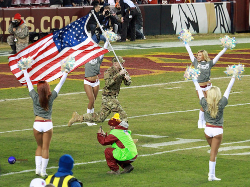 US Soldier runs on field with US Flag in front of team and cheerleaders.