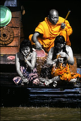 A monk performs a purification ceremony on two girls