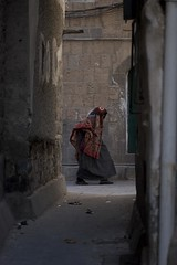IMG_8674 (mariatarasoff) Tags: yemen sanaa old city souk brick mud stone people man woman walking pointofview perspective watching looking arab arabia muslim niqab shawl traditional hijab red blue black shadows light daytime