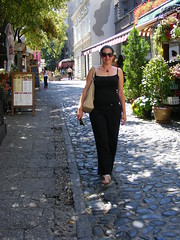 Nina at Skadarlija - Belgrade August 2016 (seanfderry-studenna) Tags: skadarlija belgrade beograd serbia srbija balkans europe european capital city street photography restaurants shops candid public people persons plants trees cobbles cobble stones path road summer august 2016 sun sunshine glasses sunglasses woman female girl lady girlfriend fiancee wife married happy smiling beauty beautiful gorgeous cute charming black clothes straps top white sandals tan tanned skin bare neck shoulders throat necklace face amrs hands pink lips brunette serb tourist vacation holiday
