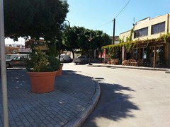 (Psinthos.Net) Tags:  psinthos village square psinthossquare psinthosvillage    villagecenter    pavement   day sunnyday light sunlight     shadow bluesky sky    pots  trees  treebranches  road greenery   umbrellas houses  noon    autumn october