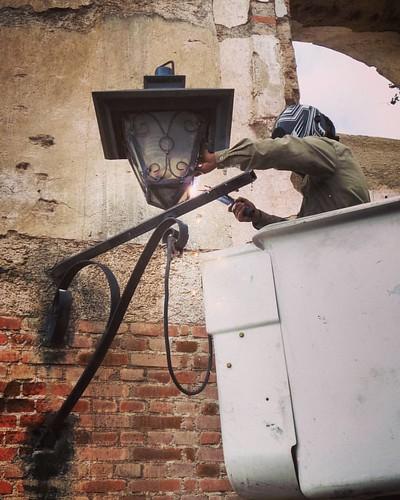 Un Power Ranger arreglando un farol en la calle del Arco
