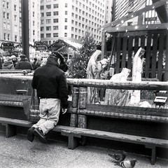 A quiet moment at Christkindlemarkt (yooperann) Tags: christmas blackandwhite holiday chicago man monochrome market praying german creche kneeling lifesize nativity chicagoist christkindlmarkt