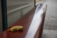 Unfinished business / Heb ei gorffen (Dai Lygad) Tags: gingerbreadman face halfeaten discarded biscuit busstop