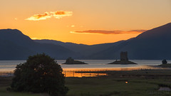 Castle Stalker veiling itself at sunset (lunaryuna) Tags: scotland westcoast landscape lake mountains lochlaich castlestalker scottishcastlesunset sundown nightfall sky clouds reflections water shore lakeshore lightmood lunaryuna