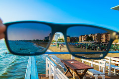 Durres beach, Albania (throughmysunglasses) Tags: city travel blue trees sea sky people sun beach water sunglasses swimming buildings table photography landscapes eyes sand creative through traveling albania glance adriatic durres plazhi throughmysunglasses durresi sandbeds