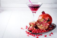 Pomegranate, cut into sections on a metal dish in the background of the shot glasses with red drink (lyule4ik) Tags: