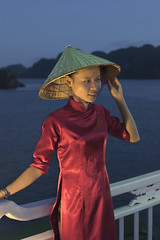 The woman in the red cheongsam (tmeallen) Tags: woman vietnamese cheongsam red cooliehat shipsrailing cruiseship night sidelight islands halongbay northvietnam