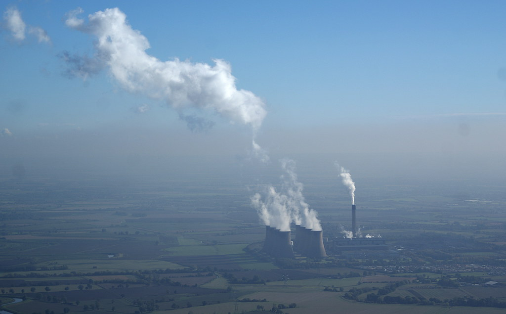 Huge power stations send smoke up through the haze layer