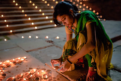 Lighting the diya (ZeNfuZZ) Tags: street 35mm river candid varanasi lamps ganga deepawali ghat earthen diya 2015